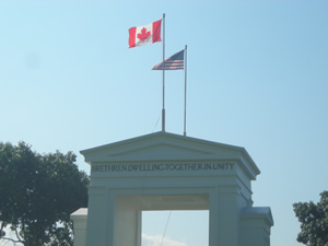 Photo: Peace Arch at the border between Canada and the United States. Atop the Peace Arch Monument are the words BRETHREN DWELLING TOGETHER IN UNITY. Photo Credit: Bradford McIntyre